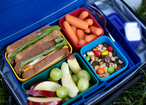 Close up of a bento-style lunch with sandwich, fruit, carrots and snack