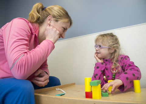 Therapist working with a little girl and blocks