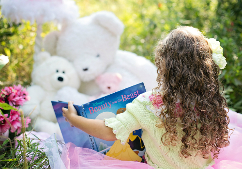 Little girl reading to her teddy bears