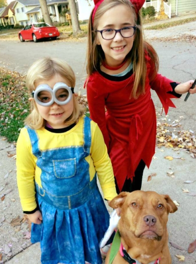 Two girls and a dog dressed for Halloween