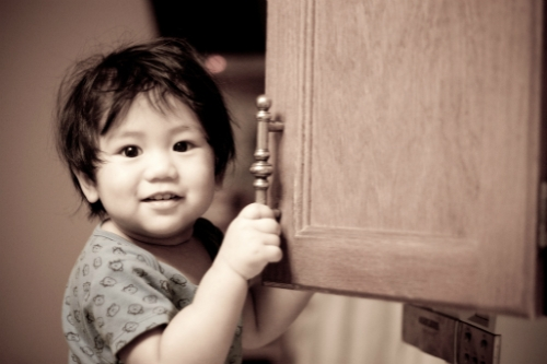 Toddler opening a cabinet