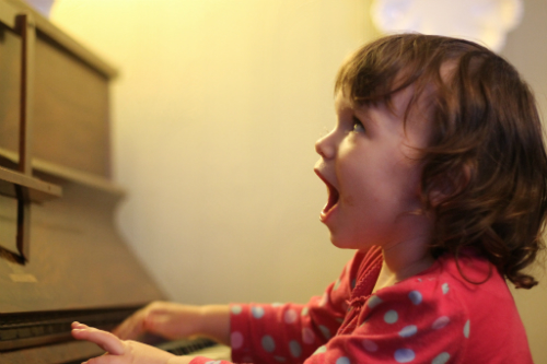 little girl singing at piano