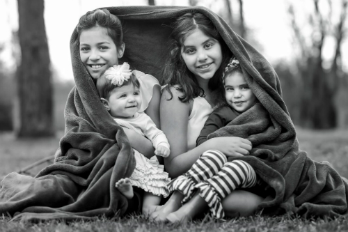 four girls cuddled under blanket