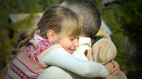 little girl hugging her dad and a teddy bear