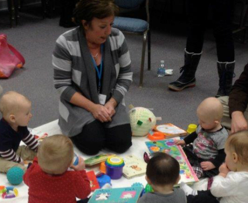 woman interacting with babies and toys