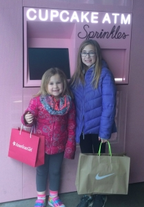 two girls in front of cupcake ATM