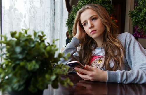 girl holding smartphone while looking out window