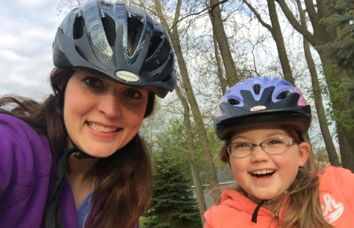 mom and daughter selfie wearing bike helmets