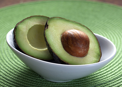 halved avocado in bowl