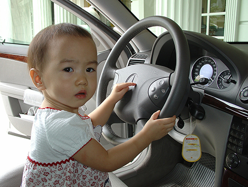 child sitting in driver's seat