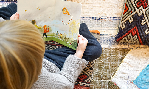 child reading book on blankets
