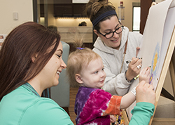 child life specialist drawing with a young patient and her mom