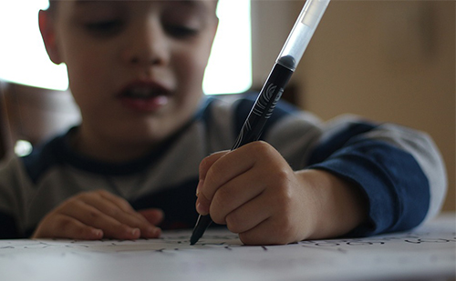young boy writing with marker