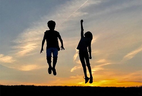 silhouette of boy and girl jumping at sunset