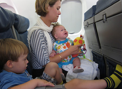 mom with baby and young boy on airplane