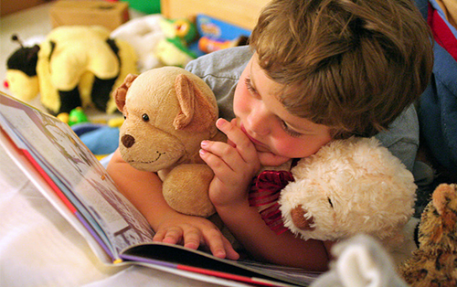 Boy reading to his stuffed animals