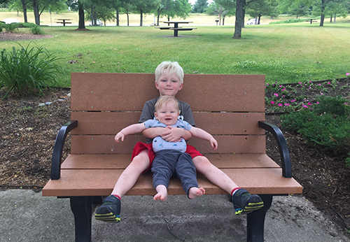 big brother holding little brother on bench