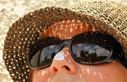 face with sunhat, sunglasses and sunscreen