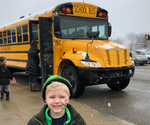 little boy standing in front of school bus