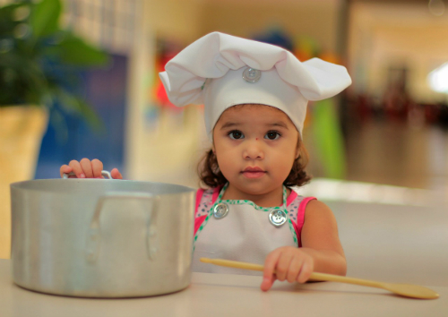 little girl in kitchen with pot, spoon and chef hat