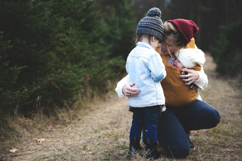 woman with baby comforting a toddler girl