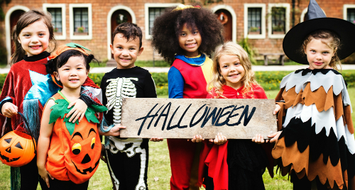 "kids in costume holding ""Halloween"" sign"