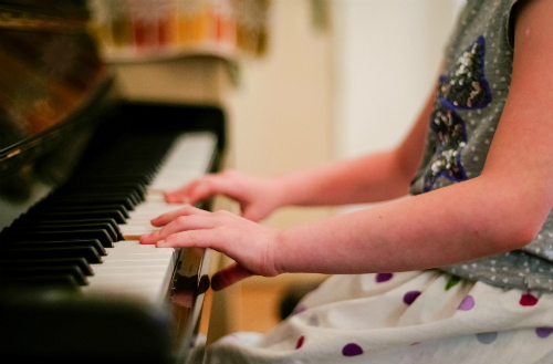 young girl hands on piano keys