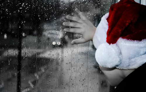 sad child wearing Santa hat looking out window at rain