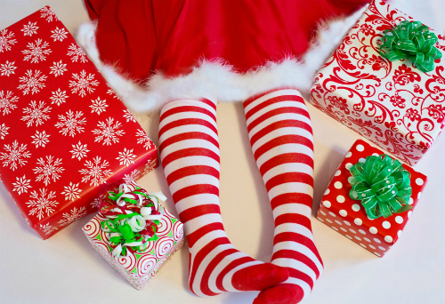 girl's legs surrounded by presents